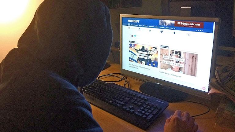Man med huvtröja vid datorskärm som visar högerextrem sajt.