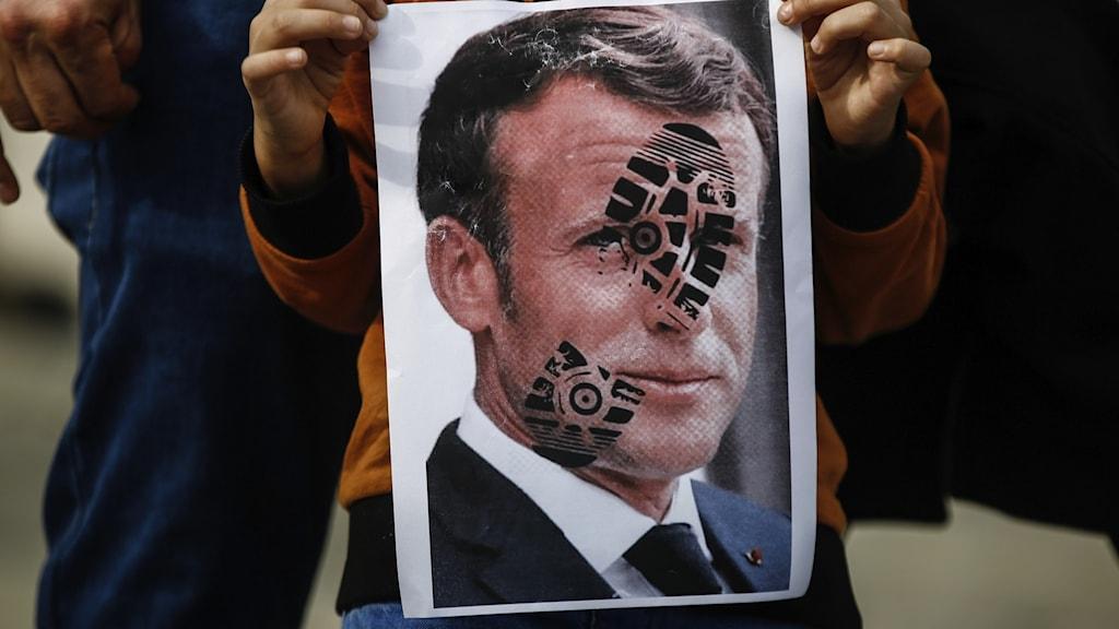 En demonstrant håller upp en bild av Frankrikes president Macron med ett fotavtryck