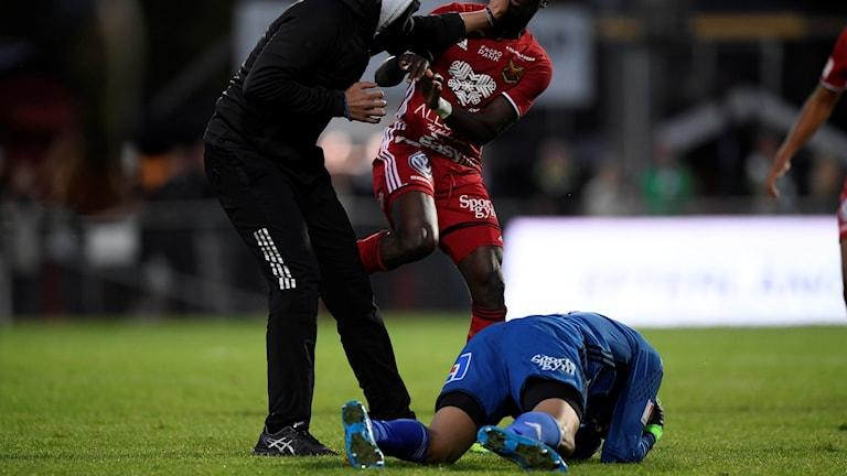 Östersunds målvakt Aly Keita knockad av en åskådare (V) som sprang in på planen under måndagens allsvenska fotbollsmatch mellan Jönköping Södra IF och Östersunds FK på Stadsparksvallen.