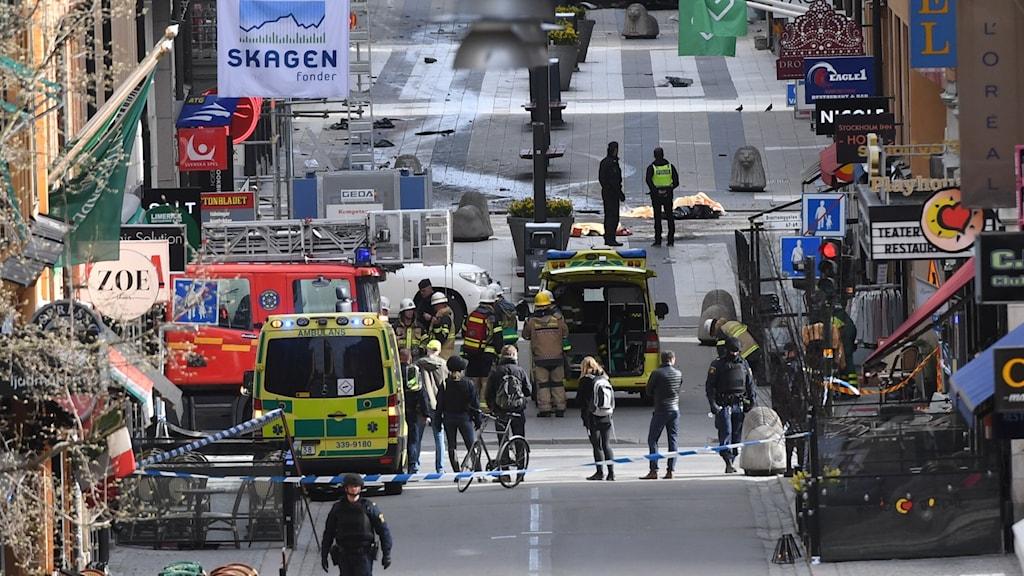 Ambulanser, räddningstjänst och människor i korsning.