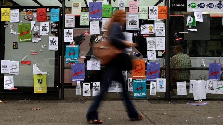 En kvinna går förbi en vägg med affischer med budskap om söndagens katalonska folkomröstning.