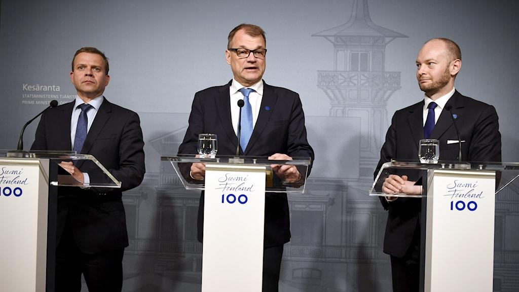 Tre män vid podium.