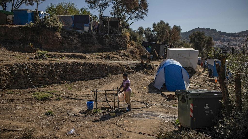 Flyktingläger, tält, någon hämtar vatten i en plastdunk