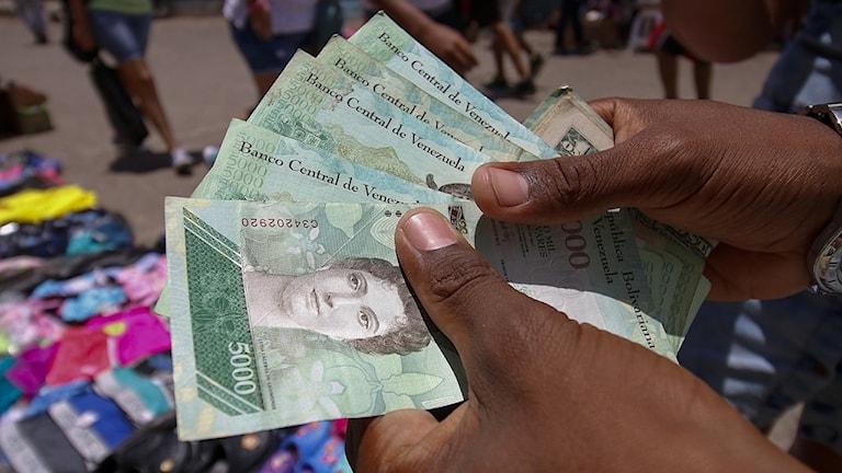 Arkivbild: Venezuelansk man håller upp sedlar.