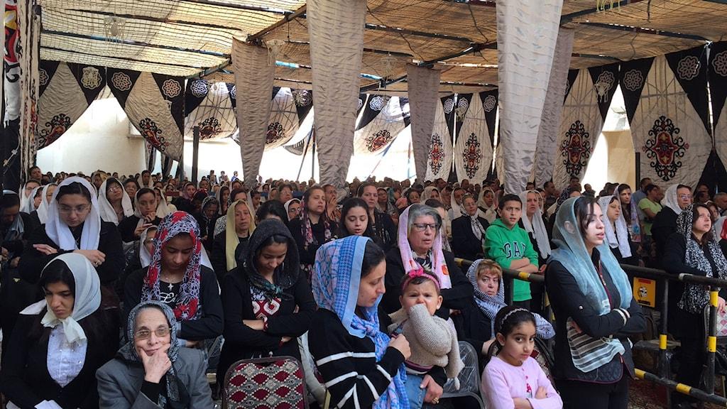 Mässan hålls i tält intill Mar Girgiskyrkan (st Göranskyrkan) som är stängd efter det blodiga attentatet. Många av kvinnorna har tunna vita sjalar med religiösa motiv, tex st göran som bekämpar Draken