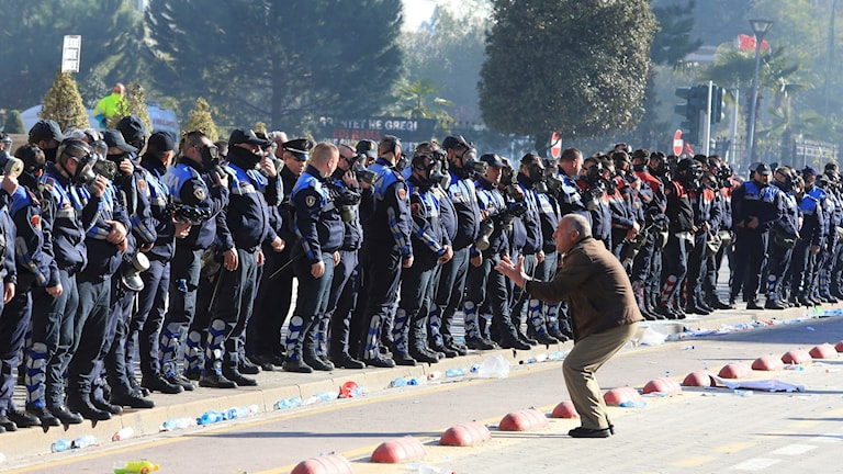 En demomnstrant framför polisstyrkor vid protesterna i Tirana.