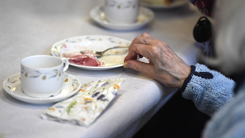 En äldre person dricker kaffe och äter tårta på ett  äldreboende