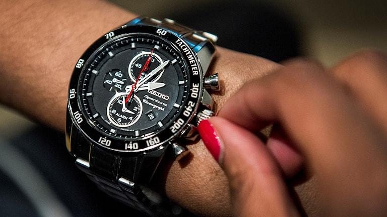Kvinna skruvar på sin klocka. Arkivbild.