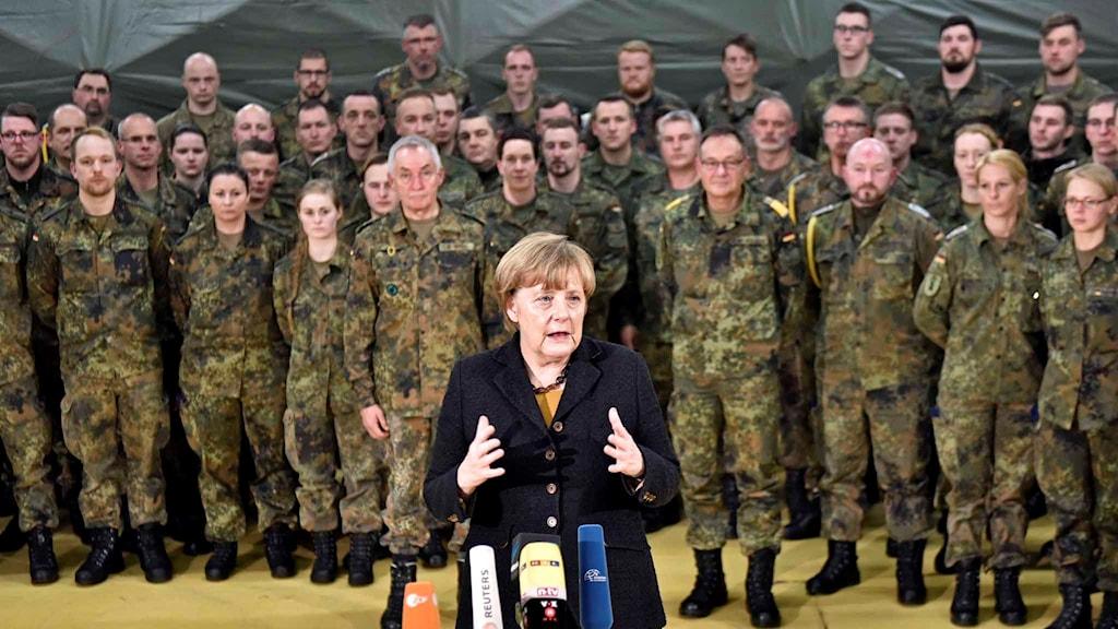 Angela Merkel håller tal, bakom henne står flera uppställda, tyska militärer.