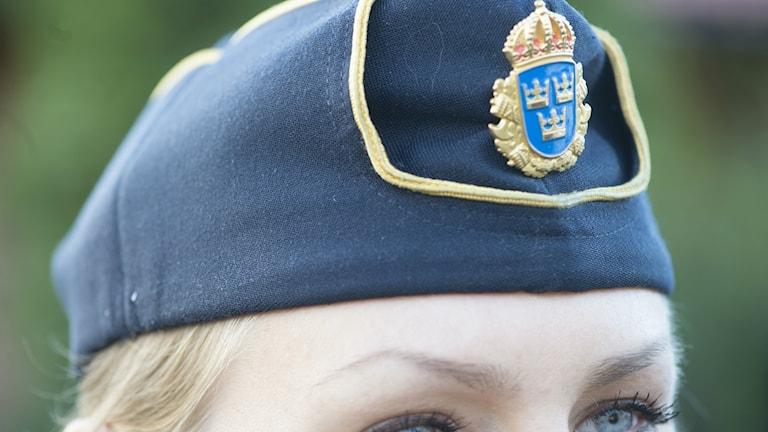 Bilden visar en blåögd kvinnlig polis med polismössa. Foto: Fredrik Sandberg/TT.