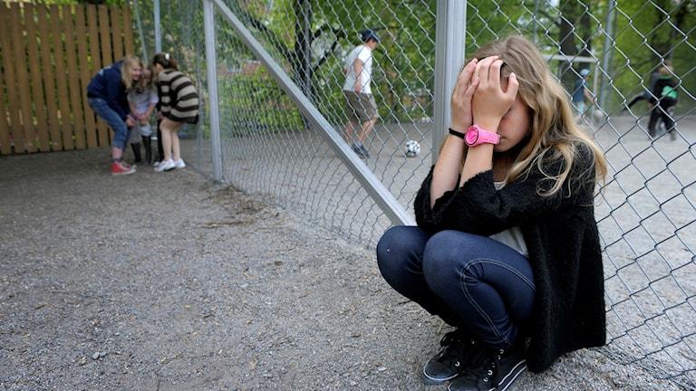 En flicka sitter ensam på en skolgård med händerna för ansiktet.