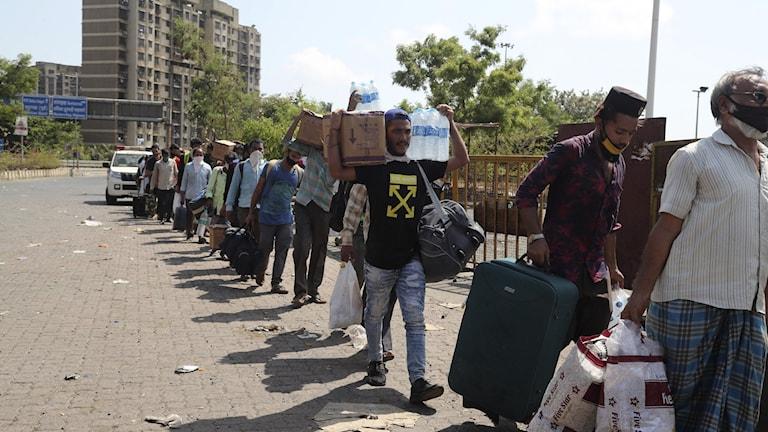 Migrantarbetare köar för att komma med ett tåg som ska ta dem hem.