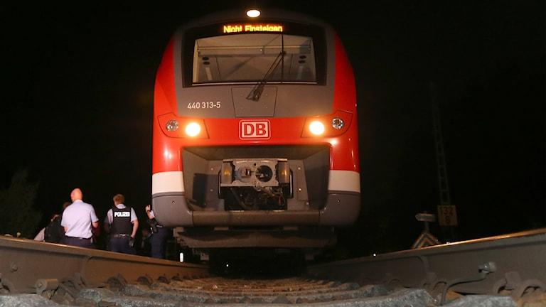 Polis står bredvid regionaltåg i Tyskland.