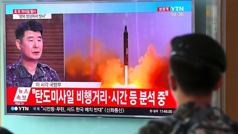 Soldat kollar på missiluppskjutning på TV.