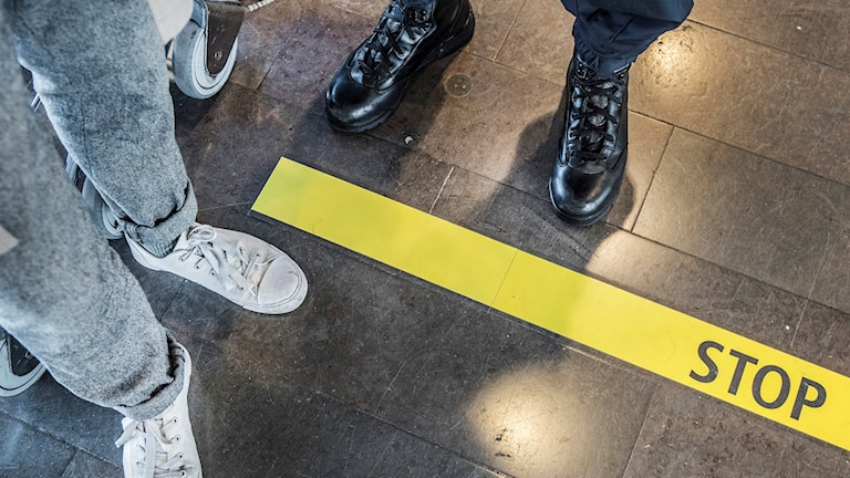 Ben och skor och en polis ben och skor. På golvet står det stopp.