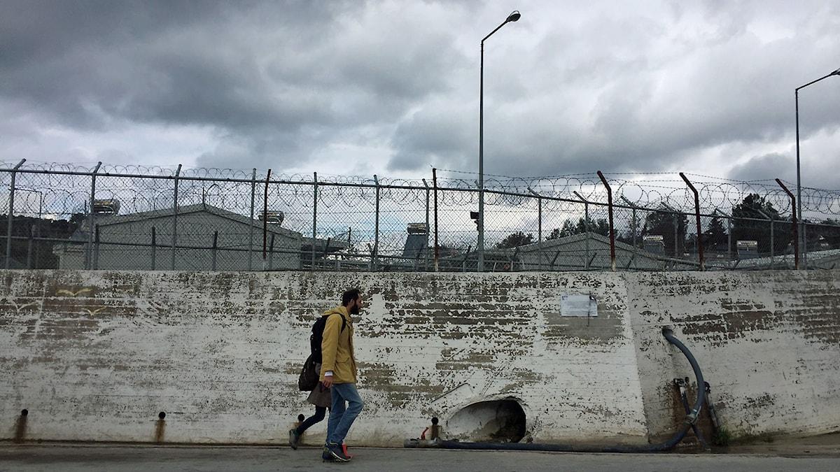 Man som går framför en mur med taggtråd.
