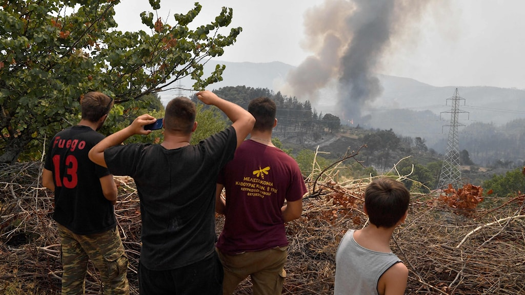 Fyra personer tittar på en brand i Grekland.