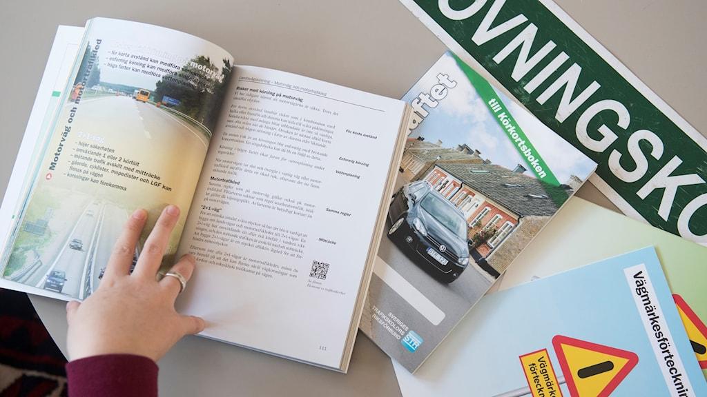 En 18-åring läser körkortsboken för att kunna ta körkort.
