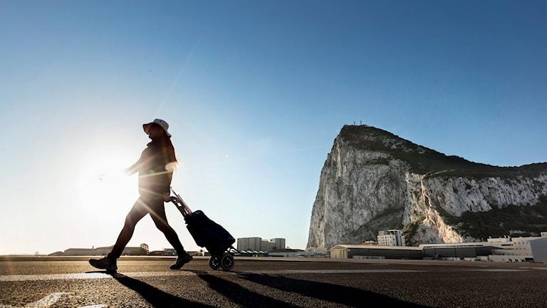 Kvinna som går från den ikoniska Gibraltarklippan.