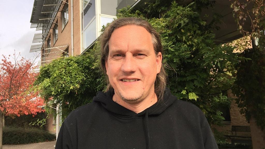 Bilden visar Tommy Andersson, professor i nationalekonomi vid Ekonomihögskolan i Lund. Han har bakåtstruket hår och har en svart tröja på sig. Han står framför en av Ekonomihögskolans byggnader, i bakgrunden ser man ett träd i höstfärger. Foto: Anna Bubenko/Sveriges Radio.