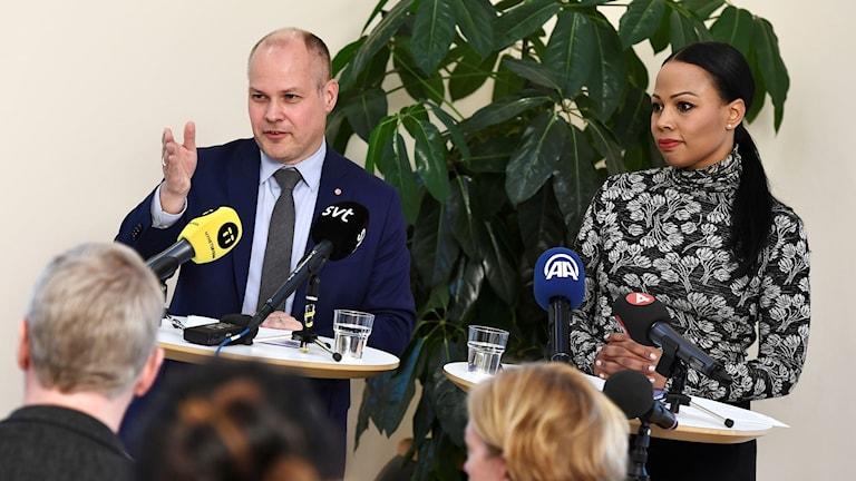 Man och en kvinna bakom mikrofoner som tillhör journalister.