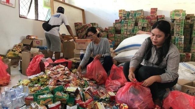 Kvinna som packar hjälppåsar till nödställda indoneser.