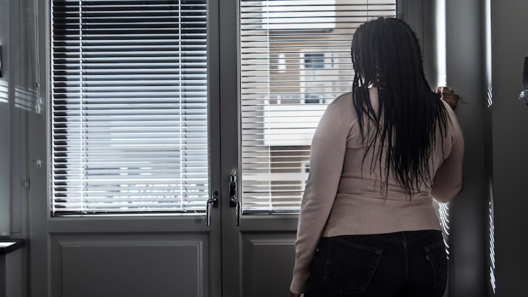 Kvinna står och tittar ut genom ett fönster med neddragna persienner.