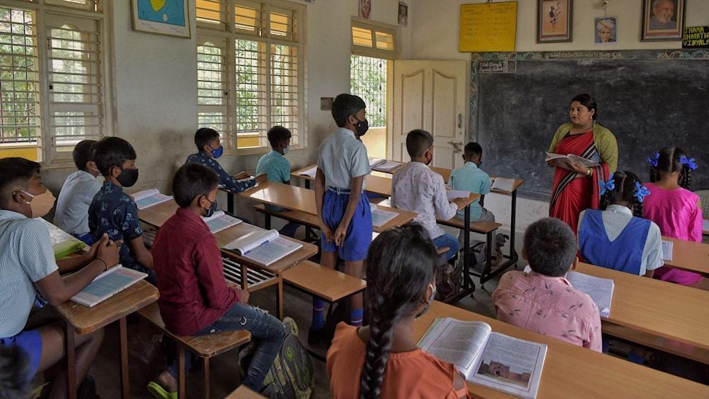 Elever med munskydd och lärare i ett klassrum i Bangalore, Indien.