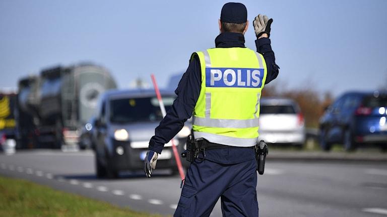 En polis framför trafik.