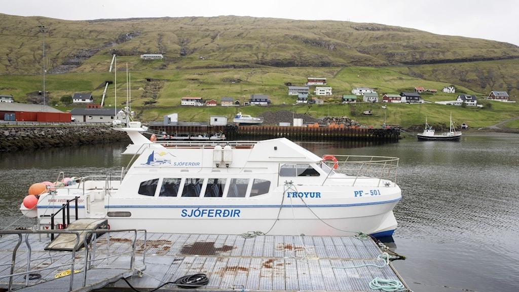 En turistbåt står vid en brygga på en av Färöarnas 18 öar.