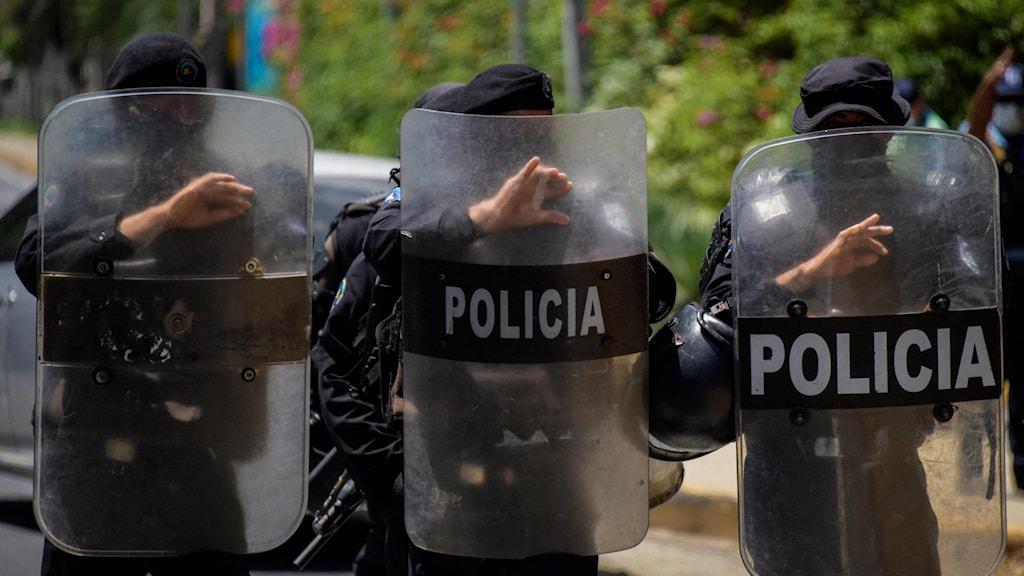 Tre poliser med sköldar.