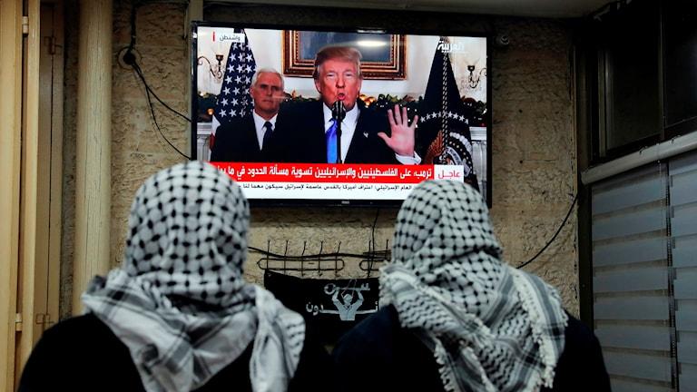 Två personer tittar på Trumps tal