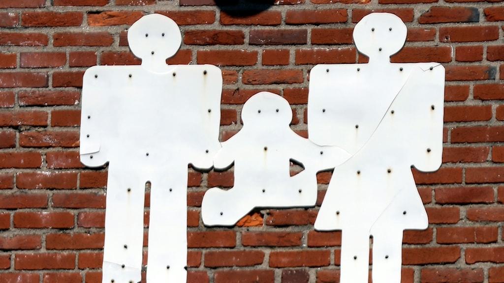Tre figurer, man, kvinna och barn.