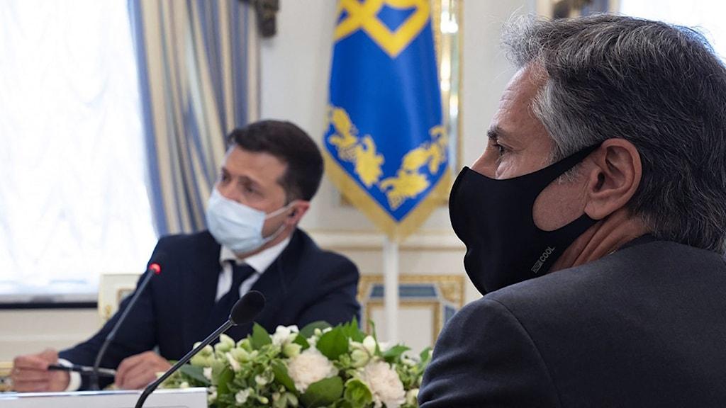 Två män i munskydd vid ett bord.