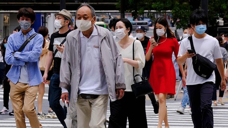 Människor på en gata i Tokyo bärandes munnskydd.