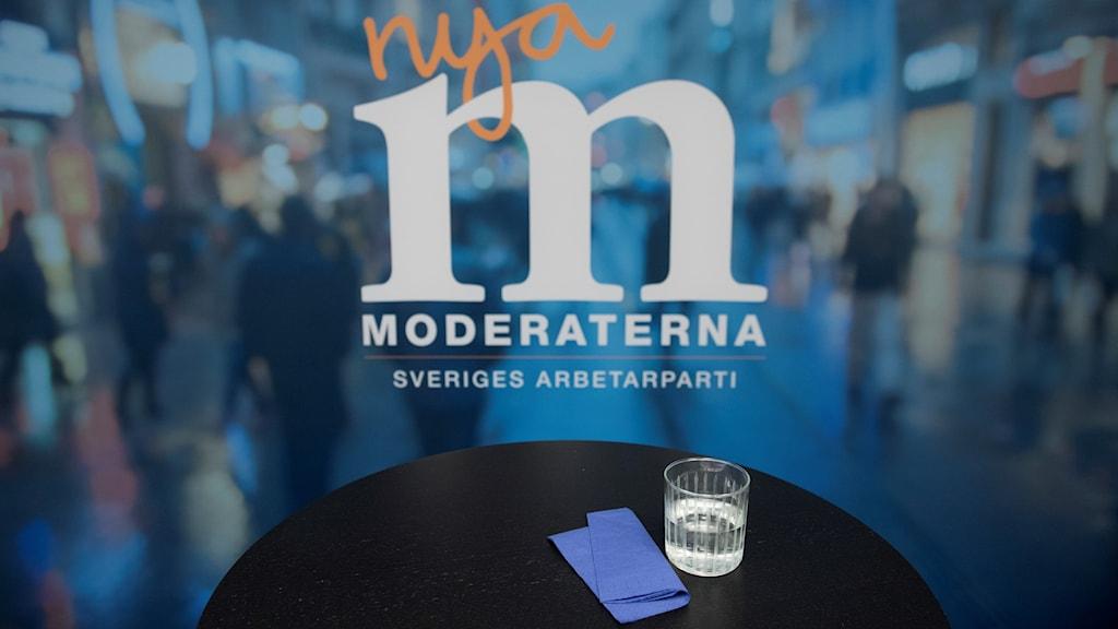 Ett ensamt bord med ett vattenglas framför en Moderat-logga.