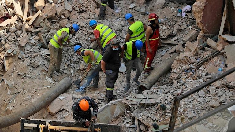 Räddningsarbetare gräver i rasmassorna i Beirut.
