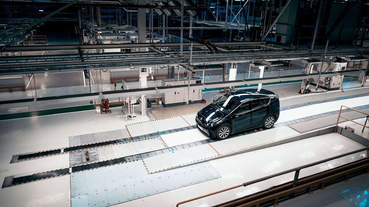 En svart elbil inne på en tom produktionslina i bilfabriken i Trollhättan