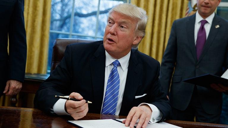 Donald Trump med en penna och ett avtal framför sig.
