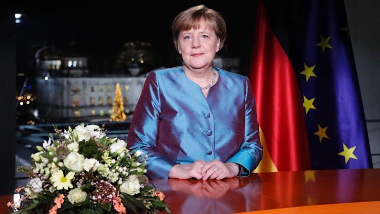 Tysklands förbundskansler Angela Merkel sitter vid ett skrivbord med blommor och bakom syns en tysk flagga och en EU-flagga.