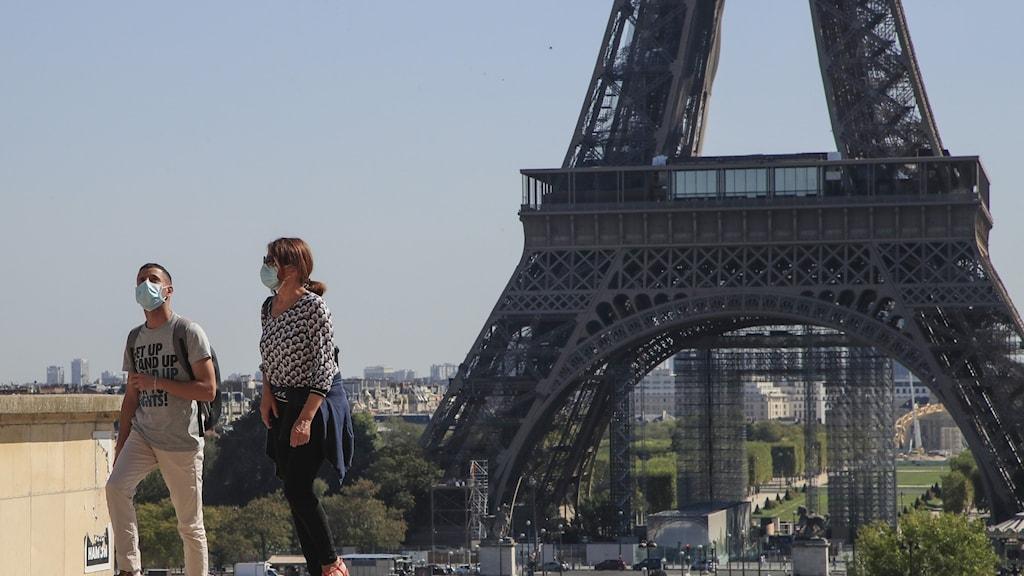 Två turister bärandes munskydd vid eifeltornet.