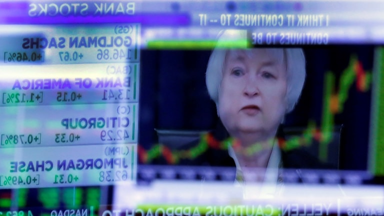 Spegelbild av Janet Yellen i en tvskärm som visar börskurser.