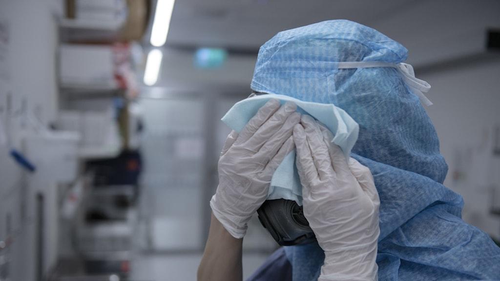 En sjuksköternska tvättar skyddsmask 90 efter passet inne på IVA-avdelningen