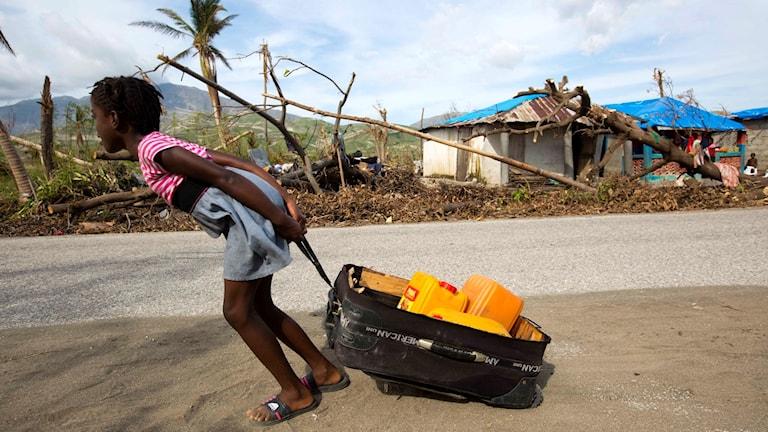 En flicka drar en väska som innehåller dunkar med vatten i Aux Coteaux, en stadsdel i Les Cayes, Haiti.