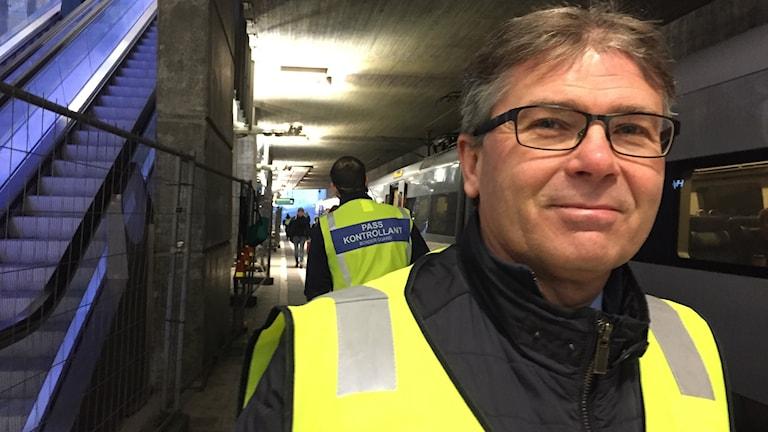 Bilden visar Michael Mattsson, chef för gränspolisen i Region Syd. Han står på tågperrongen i Hyllie i Malmö, vid ett tåg. I bakgrunden ser man ryggen på en passkontrollant som bär neonväst. Foto: Anna Bubenko/Sveriges Radio.