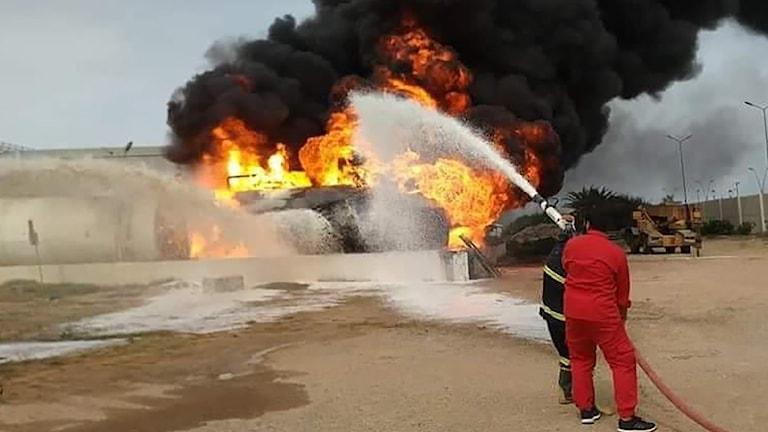 Räddningstjänst släcker en brand efter helgens attack mot Mitiga-flygplatsen i Tripoli.