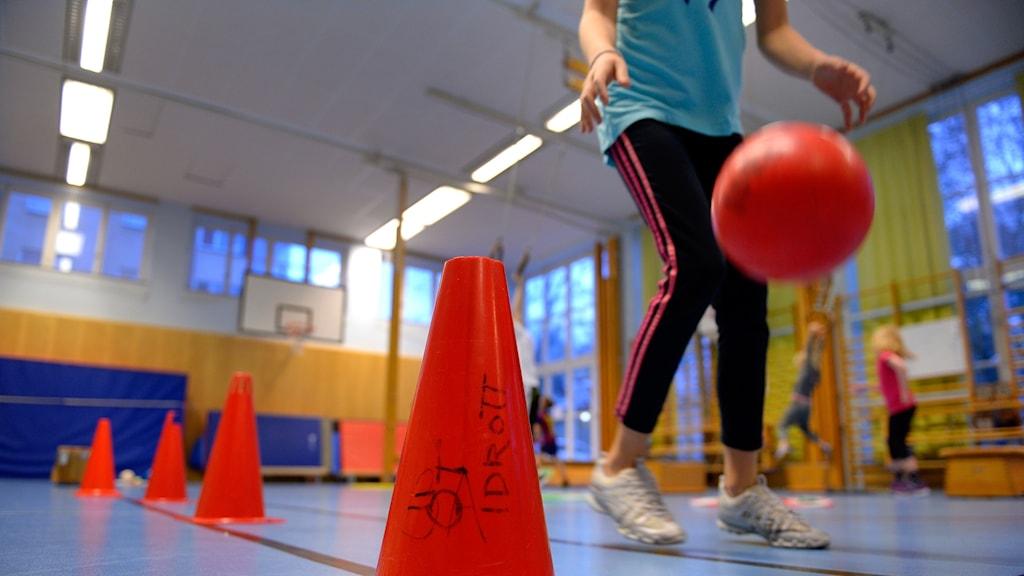 Ett barn studsar en boll i en gymnastiksal.