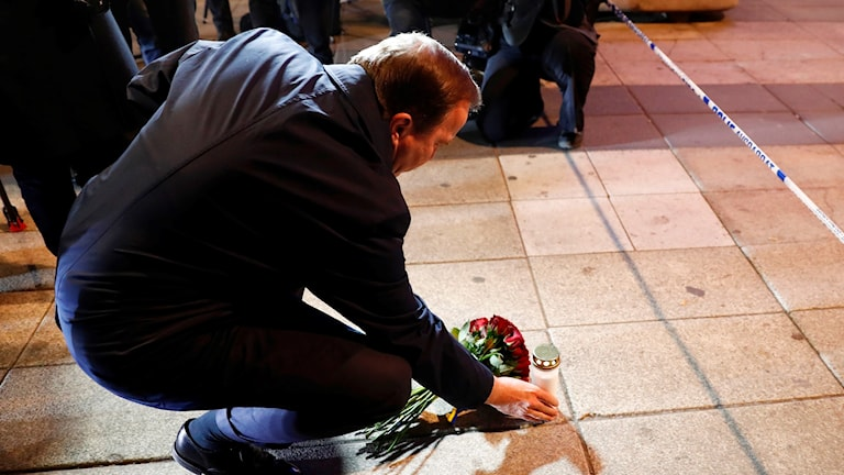 Prime Minister Stefan Löfven placing flowers and lighting a candle at the scene of the attack.