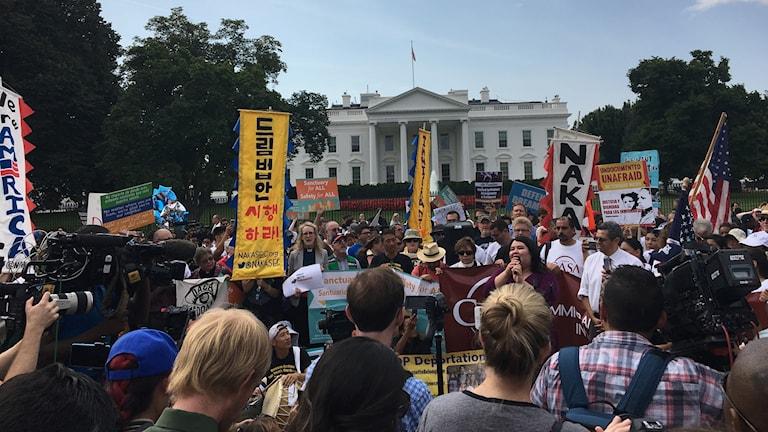 Människor demonstrerar framför vita huset.