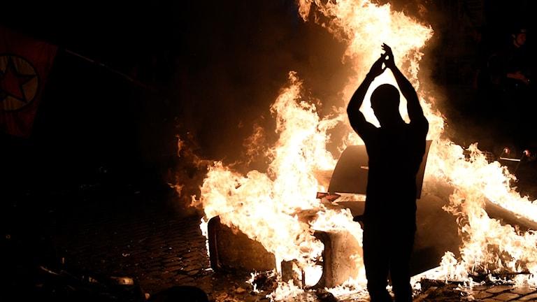 Demonstrant kastar trä på brinnande eld vid G20-mötet i Hamburg.